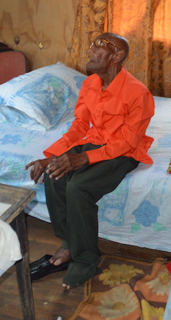 Clement Holdipp sitting on his bed in the house where he has lived for over two decades.