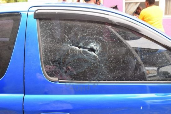 The passenger's side window of a car that was pierced by bullets during a shootout in Wotton, Christ Church.