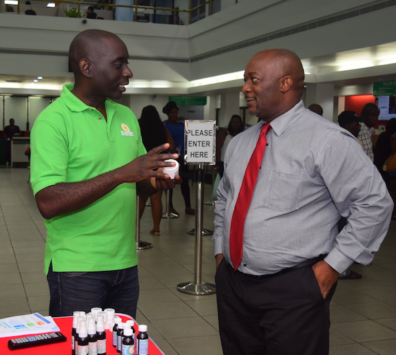 Owner of Miracle Balm Carlos Jones (left) speaking with branch manager for retail banking and central services at First Citizens (Barbados) Ltd's Bridgetown location.