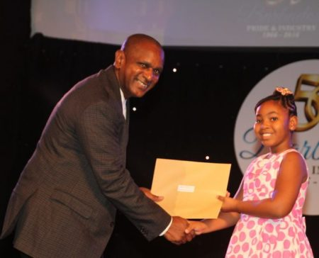 Junior Monarch in the 8-12 category, Summa Sargeant, being awarded by chairman of the Barbados Tourism Marketing Inc Alvin Jemmott.