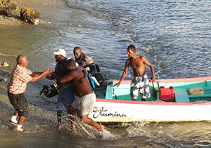 Rennie Richardson, second from left, arrives on his boat Stamina, at Plymouth, Tobago, on Friday.