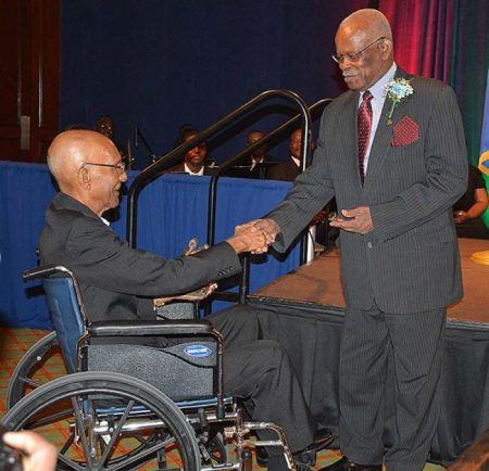 Governor General Sir Elliott Belgrave shakes the hand of Pastor Donald Stanton after presenting him with his Lydia Dowdye-Mings Servanthood Award.
