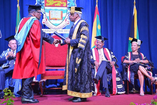 Tony Best receives his honourary degree from UWI Chancellor Sir George Alleyne.