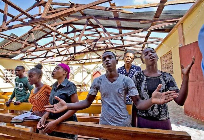Haitians worship at L'Elise de Dieu in Morne la Source, Haiti, which lost its roof in Hurricane Matthew - . Photo Credit- Patrick Farrell – Miami Herald.