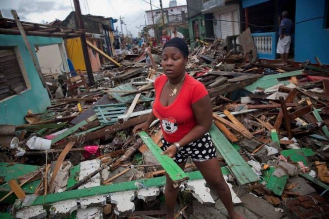 A woman removes debris from homes that fell in the street after the passage of Hurricane Matthew in Baracoa, Cuba.(Ramon Espinosa/AP)