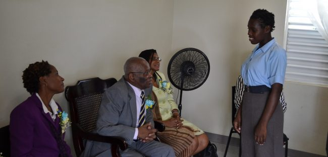 Governor General Sir Elliott Belgrave converses with 14-year-old student Akela Gibson-Foster in the presence of Principal Emelda Bell.