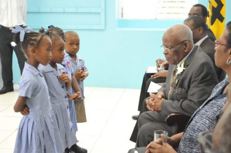 Governor General Sir Elliott Belgrave listening attentively to the students.