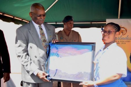 Head girl at the Springer Memorial Secondary School, Leann Toppin gifts Governor General Sir Elliott Belgrave with a painting.