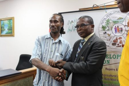 Joseph Hackett (left) was presented with an award by Minister of Housing and Lands Denis Kellman for his commitment to the area of agriculture.