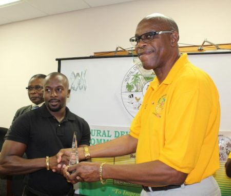 Director of the RDC Rondalph Outram presenting RDC loan recipient Ronald Sealy with an award for his commitment to agriculture.