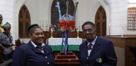 Patricia Greenidge, secretary of the Berea Pathfinder Club, and Evelyn Mayers, assistant Pathfinder director, proudly stand by the Broken Trident on display at the St Anne's Anglican Church.