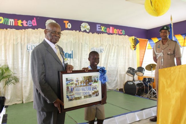 Headboy Brandon Byer-Maloney presenting the Governor General with a gift.