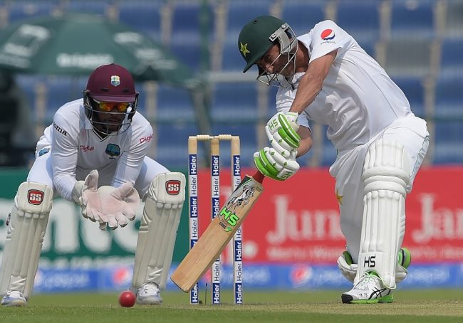 Younis Khan driving for another boundary as wicketkeeper,  Shai Hope, looks on.