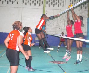 Rhe-Ann Niles of Pan American Life Insurance Warrens Sports Club spikes hard over Toners' defence.  (Pictures by Morissa Lindsay)