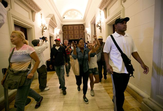 Pro-government supporters force their way into the National Assembly in Caracas, Venezuela, Sunday, Oct. 23, 2016. The government supporters interrupted a special congressional session where lawmakers were discussing bringing legal charges against President Nicolas Maduro. (AP Photo/Ariana Cubillos)