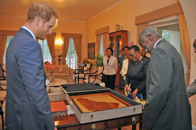 Britain's Prince Harry (left) accepting a map of Barbados in mahogany from Prime Minister Freundel Stuart on behalf of Queen Elizabeth II.