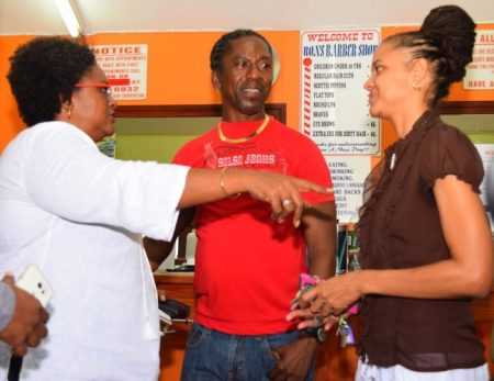 Opposition Leader Mia Mottley (left) and St Michael South East representative Santia Bradshaw (right) in discussion with barber Ronald Knight who has been operating in the vanstand for 19 years.