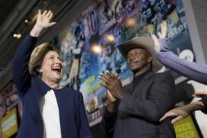 Democratic presidential candidate Hillary Clinton (left), accompanied by retired Pittsburgh Steelers Mel Blount (right), takes the stage at a rally at Heinz Field in Pittsburgh, Friday.
