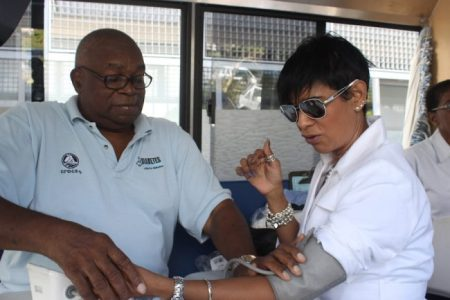 General Manager of Retail Banking for Republic Bank, Sharon Zephirinhaving her blood pressure tested by a volunteer at the Mobile Testing Unit.