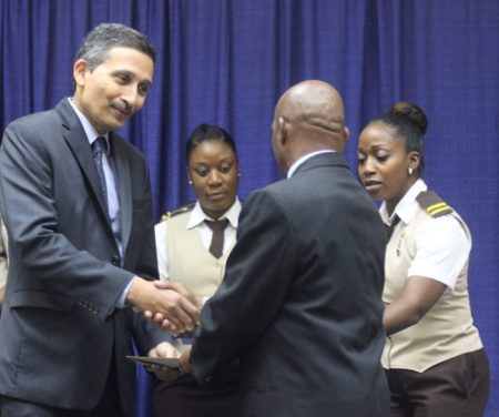 Peter Adams (left) collects his certificate from immigration officials.