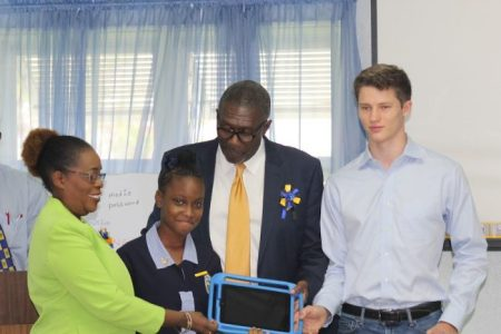 Principal of Ellerton Primary School Donna Allman receives an iPad with her student and previous Khan Academy alumni, Destynee Walkes, from Parliamentary Secretary in the Ministry of Education Senator Harcourt Husbands and Alex Eiden of Khan Academy.