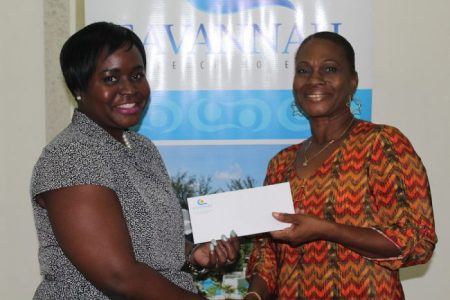Tricia Greaves, general manager of the Savannah Hotel, presents inspirational cancer survivor Shorma James with a voucher for a staycation at the Savannah Hotel.