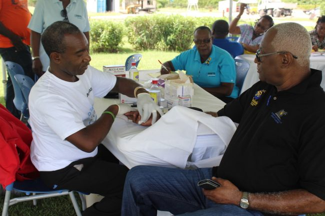 Health, Safety, Security and Environment Officer at BNOC Ltd Patrick Welch (right) getting one of his health checks done from volunteer with the Diabetes Association of Barbados Victor Worrell.