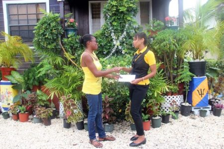 Second prize winner Patricia Phillips receiving her vouchers from the UDC's Paula Gall.