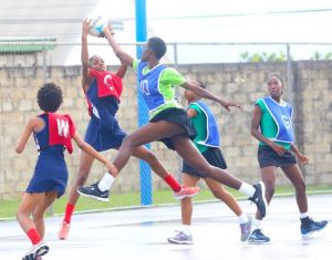Queen's College's center Janina Haynes reaches to take a good catch ahead of the challenge from Lester Vaughan's wing-defence Kayla Codrington. (Picture by Morissa Lindsay)