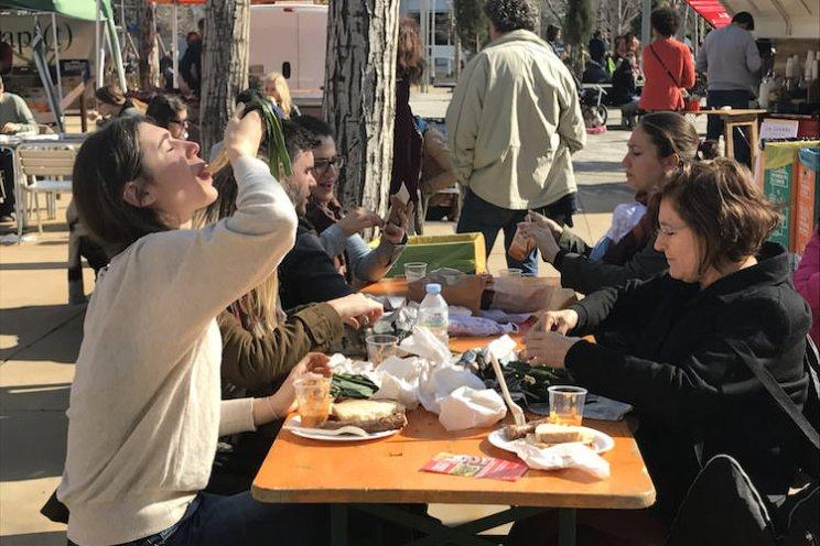 Mensen eten calçots bij de Mercat de la Terra markt in Barcelona