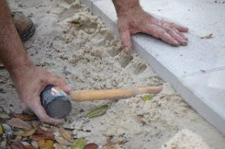 you can use the end of your mallet to push sand underneath to make it even_small