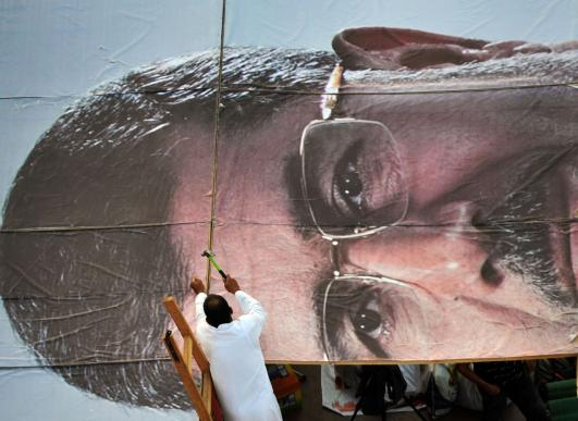 An Egyptian supporter of deposed president Mohamed Morsi builds a giant portrait of him as Morsi's supporters continue to hold a sit-in outside Rabaa al-Adawiya mosque on July 25, 2013 in Cairo