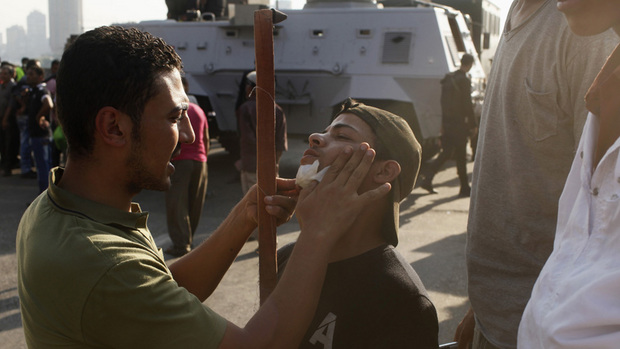An opponent of deposed President Mursi, dresses wound of another injured in Monday's clashes with pro-Mursi protesters  in Cairo