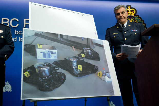 RCMP Chief Supt. Wayne Rideout looks at a photograph of pressure cookers that RCMP say two people intended to use as explosive devices