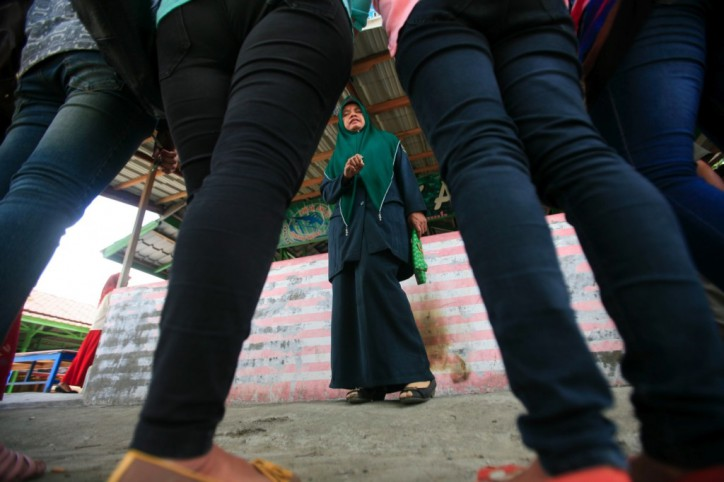 A Sharia policewoman lectures woman who were arrested for wearing tight jeans during a Sharia police raid in Banda Aceh