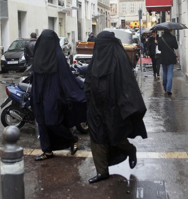 Women wearing niqabs walk on the street in Marseille