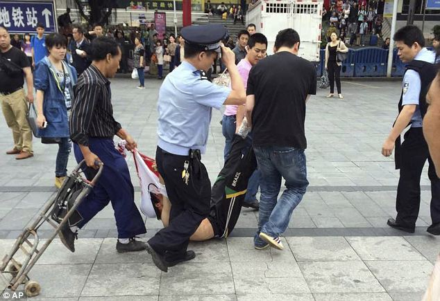 In this photo taken by a mobile phone, a suspected assailant is taken away after being subdued in an attack at a railway station in Guangzhou