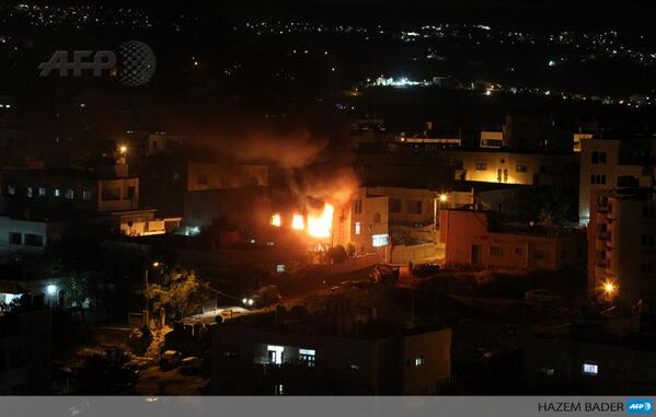 Flames billow from the blown-up house of Amer Abu Eisheh, a suspect in the killing of three kidnapped Israelis