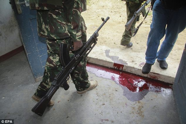 A police officer walks past blood stains on the ground at the Gamba police station in Gamba