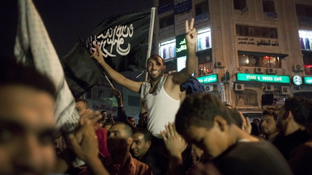 """Palestinians dance while flying a Palestinian Islamic Jihad Movement flag reading in Arabic """"there is only one God and Muhammad is his prophet,"""" during celebrations in the West Bank city of Ramallah"""