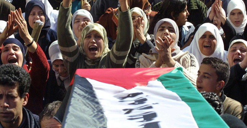 Women shout as they follow an empty coffin for Palestinian suicide bomber Wafa Idris during her symbolic funeral through the streets of the al-Amari refugee camp to a cemetery in the nearby West Bank town of Ramallah