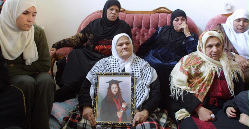 Wasfiyeh Idris, the mother of suicide bomber Wafa Idris, surrounded by other female family members, holds a portrait of her daughter at her home in the al-Amari refugee camp near the West Bank town of Ramallah 30 January, 2002. Idris believed to be the first ever female Palestinian suicide bomber, blew herself up in central Jerusalem 27 January, killing an elderly Israeli man in an attack claimed by the al-Aqsa Martyrs' Brigades, a radical offshoot of Palestinian leader Yasser Arafat's Fatah movement.