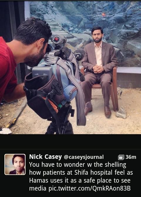 Mushir Al Masri, a Hamas MP and media spokesman, being interviewed by media in front of backdrop showing a destroyed house, and being filmed inside the Al Shifa hospital in Gaza. The photo was posted on Twitter by WSJ correspondent Nick Casey, and has since been removed.