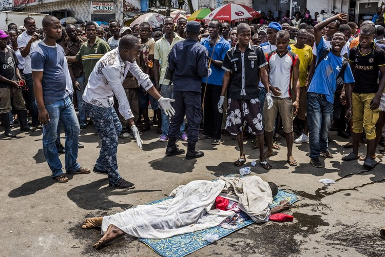 Residents look on as the body of a man suspected of dying from Ebola lies in a busy street, after it was reportedly dragged there to draw attention to burial teams following days of failed attempts by his family to have his body picked up, in Monrovia, Li