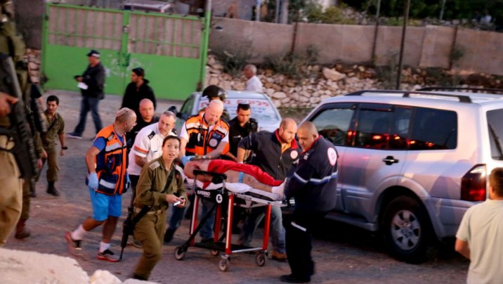 Israeli security and rescue personnel seen with the terrorist who was shot after a deadly stabbing attack at a bus stop at the entrance to the Israeli settlement of Alon Shvut