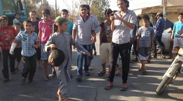 ISIS niño que lleva la cabeza decapitada