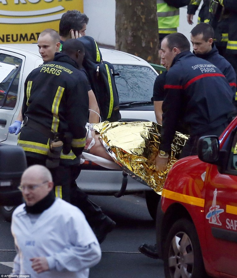 Rescue service workers evacuate injured person on a stretcher after the shooting in Montrouge which left a female police officer dead
