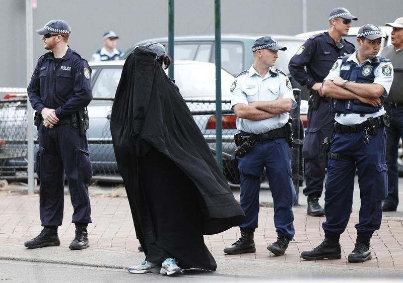 Police officers stand on guard next to a woman wearing a burqa near the venue where controversial Dutch member of parliament Geert Wilders will speak in the Sydney suburb of Liverpool