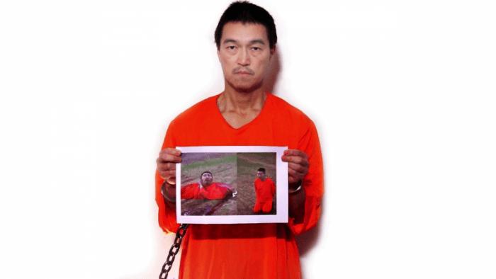 Kenji Goto holding up photo of a beheaded Haruna Yukawa