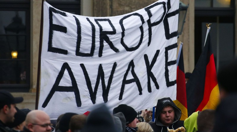 Members of the movement of Patriotic Europeans Against the Islamisation of the West (PEGIDA) hold flags and banners during a PEGIDA demonstration march in Dresden